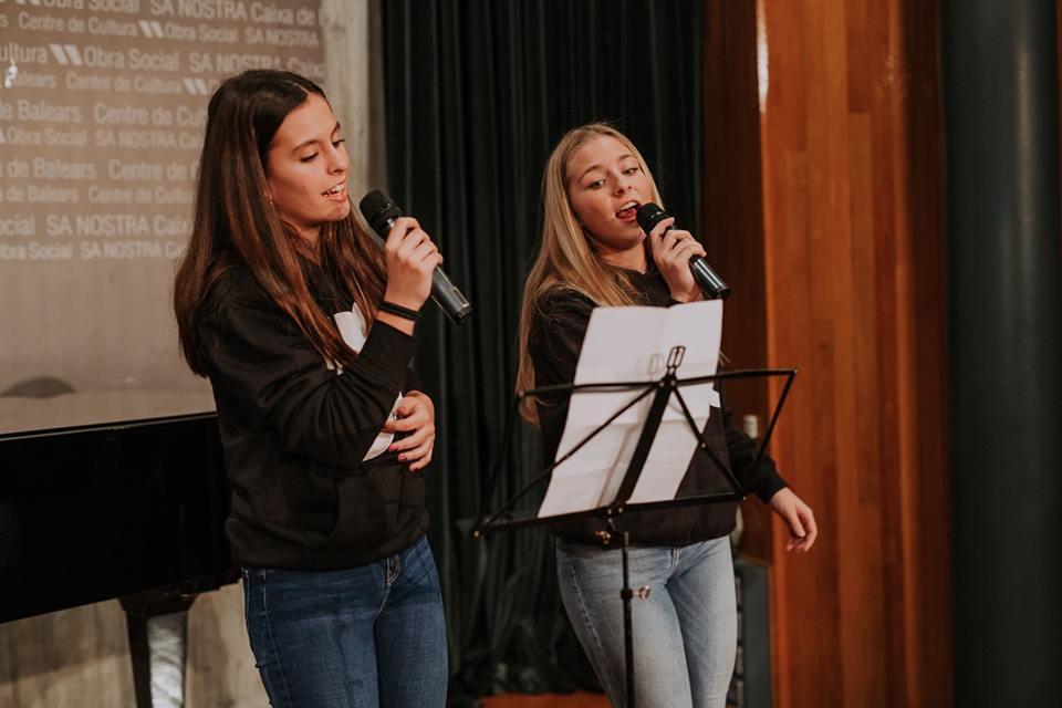amigas compartiendo escenario en el concierto de la escuela de música renacimiento